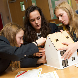 Students building a house from cardboard